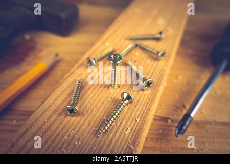Screws, screwdriver, hammer and a pencil on a wood table. Concept tools and repair work.