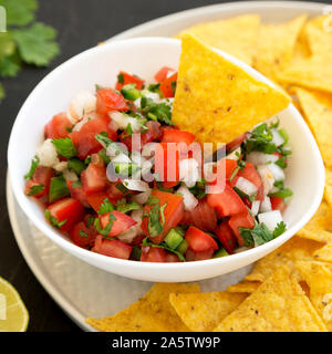Pico de Gallo with gluten free tortilla chips on a black background, low angle view. Closeup. - Stock Photo