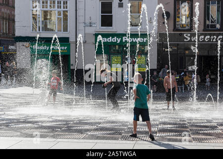 Children cool off playing in Liverpool city centre fountains. - Stock Photo