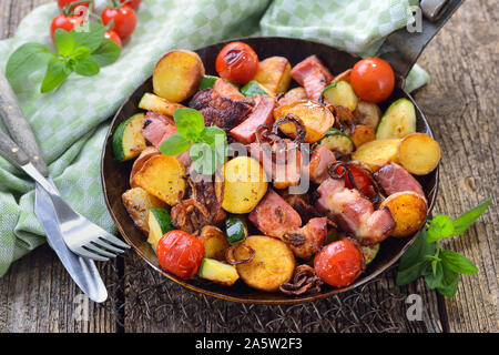 A filling meal: Fried unpeeled baby potatoes with cured pork neck and vegetables, served in an iron frying pan - Stock Photo