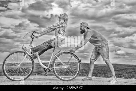 Man helps keep balance and ride bike. How to learn to ride bike as adult. Girl cycling while boyfriend support her. Woman rides bicycle sky background. Cycling technique. Learn cycling with support. - Stock Photo