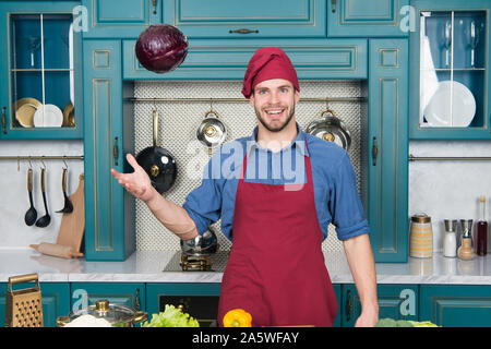 Catch it. Handsome cook in kitchen. Chef following recipe. Cooking dinner with traditional recipe. Preparing meal. Healthy food. Professional kitchen. Traditional cuisine. Man at kitchen concept.