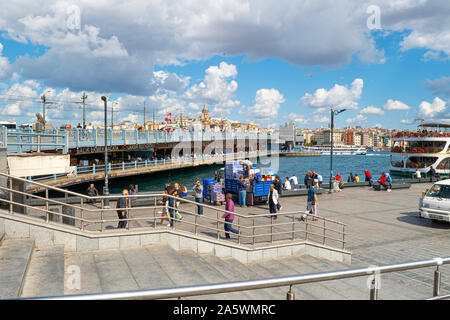 Tourists and local Turks near the ferry port at the Galata Bridge over the Bosphorus, with the Galata Tower in view. - Stock Photo