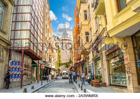 A colorful, busy street of cafes, shops people and a stray cat with the Galata Tower behind, in Istanbul, Turkey. - Stock Photo