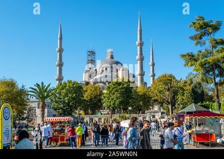 Tourists and local Turks enjoy a sunny day in Sultanahmet Square among the roasted corn cob food vendor stands and the Blue Mosque behind - Stock Photo