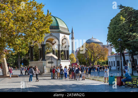 Tourists pass by the German Fountain, a gazebo styled fountain in Sultanahmet Square with the Hagia Sophia in the distance - Stock Photo