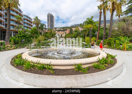 The sloping, landscaped Casino Gardens and water fountain designed by Adouard Andre, with the city behind in Monte Carlo, Monaco. - Stock Photo