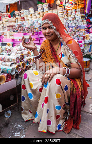 A portrait of a woman working in a market selling bangles and drinking chai, Jodhpur, Rajasthan, India. - Stock Photo