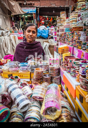 A portrait of a young woman working in an open air market in Jodhpur, Rajasthan, India selling bangles. - Stock Photo
