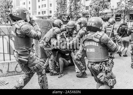 A group of 'Carabineros' Police arresting a protester in Plaza Italia square during latest October 2019 riots in Santiago de Chile city streets - Stock Photo