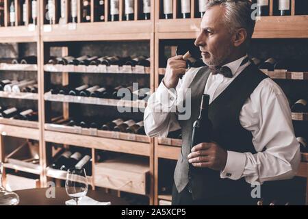 Sommelier Concept. Senior man standing opening wine bottle smelling cork pensive - Stock Photo