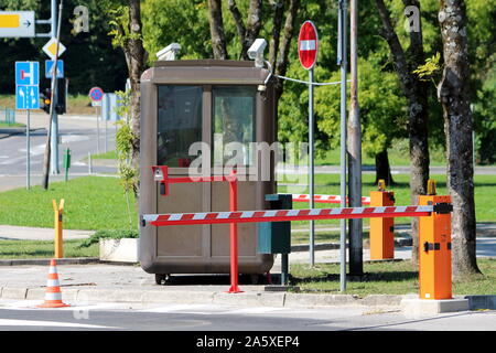 Dark brown metal security post with two close circuit TV CCTV security surveillance cameras on top surrounded with closed red and white barriers - Stock Photo