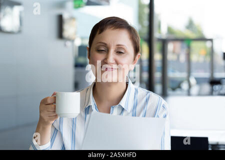 Business woman holding paperwork and having a cup of coffee in the office. - Stock Photo