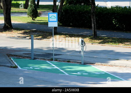 Two designated green parking places with electric cars charging stations at local public parking surrounded with paved road and trees on warm sunny - Stock Photo