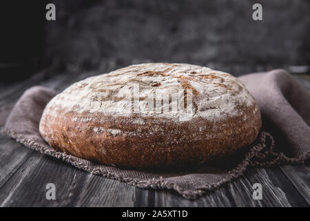 A homemade round levain bread with rye and wheat flour. that is laid on a dark wooden table, with a dark background. There is a brown soft linen cloth