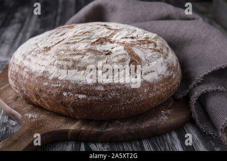A homemade round levain bread with rye and wheat flour. that is laid on a dark wooden table, with a dark background. There is a round cutting board un