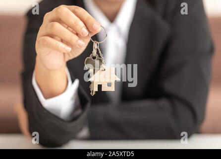 Hand of a woman holding a wooden model house and a key showing to the front. The human wearing a black suit and sitting on the sofa. - Stock Photo