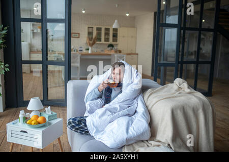 Man feeling cold so drinking hot tea and covering in bedsheet - Stock Photo