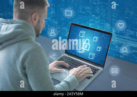 Concept of online security. Guy work on computer with conceptual icons of security, social networks, file sharing, mail, search. - Stock Photo