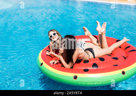 Aerial view of two womenlying on inflatable watermelon mattrass floating and relaxing in swimming pool - Stock Photo