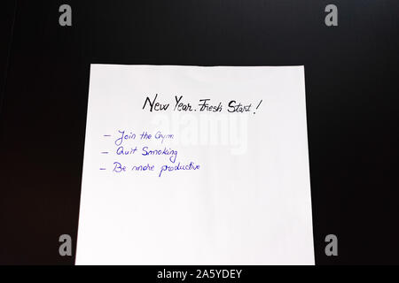 Writing New Year`s Resolutions. Christmas Resolutions. Text New Year`s Resolutions on paper. New Year, New Start text. - Stock Photo