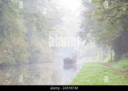 Stourbridge, UK. 23rd October, 2019. UK weather: heavy fog slows down traffic for commuters today, although some travellers are used to the slow speed of commuting as we see an isolated UK narrowboat appear in the 'slow' lane of a British canal through the early morning mist. Credit: Lee Hudson/Alamy Live News - Stock Photo