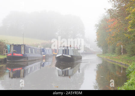 Stourbridge, UK. 23rd October, 2019. UK weather: heavy fog slows down traffic for commuters today, although some travellers are used to the slow speed of commuting as we see a UK narrowboat making its way in the 'slow' lane of a british canal, moving slowly through the early  morning mist. Credit: Lee Hudson/Alamy Live News - Stock Photo