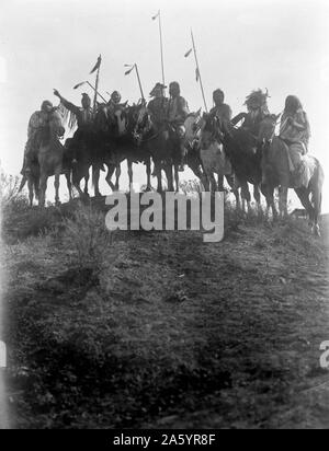 Photographic print of eight Crow Indians on horseback, silhouetted on top of hill. Photographed by Edward S. Curtis (1868-1952) American ethnologist and photographer of the American West and of Native American peoples. Dated 1908 - Stock Photo