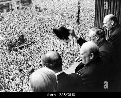 Photograph of Sir Winston Churchill (1874-1965) British statesman who was the Prime Minister of the United Kingdom, looking out over crowds celebrating the end of the Second World War in London. Dated 1945