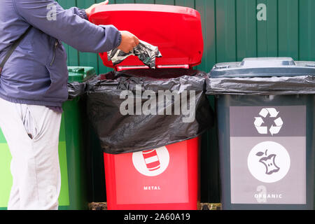 Throw metal into a container for recycling. Containers for metal, glass, paper, organics, plastic for further processing of garbage. Separate garbage - Stock Photo