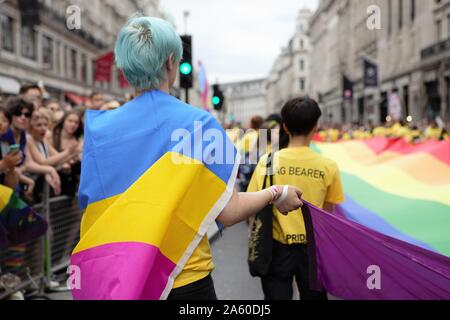 London, UK. 6th July, 2019. Pride steward wrapped in a Pride flag during the parade.The 50th Pride Parade toke place through Central London with over one million participants. Credit: Pietro Recchia/SOPA Images/ZUMA Wire/Alamy Live News - Stock Photo