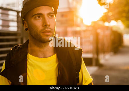 Portrait of pierced young man at backlight - Stock Photo