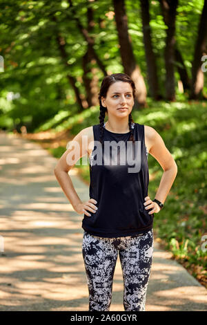 Portrait of sporty young woman in forest - Stock Photo