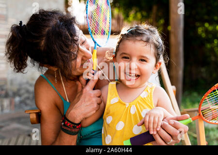 Grandmother playing with little girl and badminton rackets outdoors