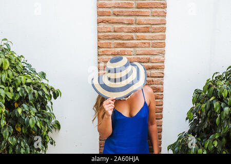Woman wearing blue dress and straw hat standing in front of wall, Nerja, Spain - Stock Photo