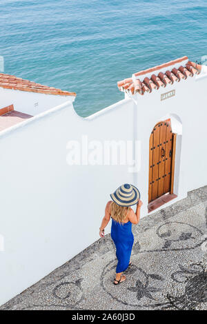Back view of woman wearing blue dress and straw hat walking along alley, Nerja, Spain - Stock Photo