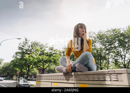 Young woman sitting on a box in the city - Stock Photo