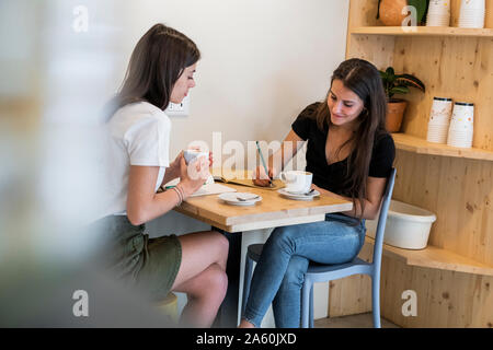 Two young women taking notes in a cafe