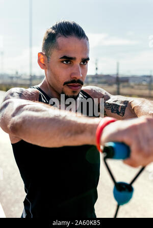 Portrait of young man exercising with expander