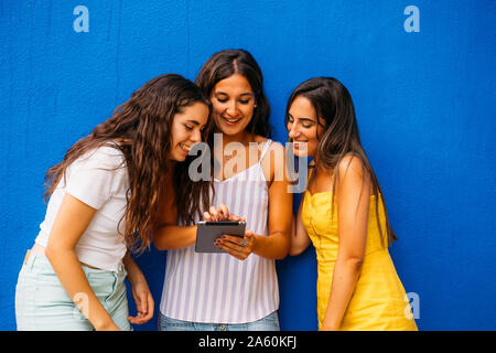 Three happy female friends standing at a blue wall sharing tablet - Stock Photo
