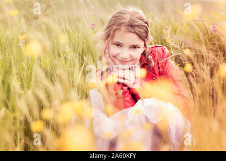 Portrait of smiling girl wearing red leather jacket crouching in flower meadow - Stock Photo