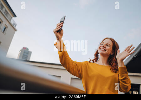 Smiling redheaded woman using cell phone on roof terrace