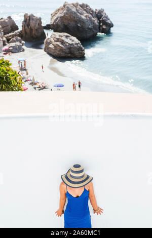 Woman wearing blue dress and straw hat standing in front of white wall, Nerja, Spain - Stock Photo