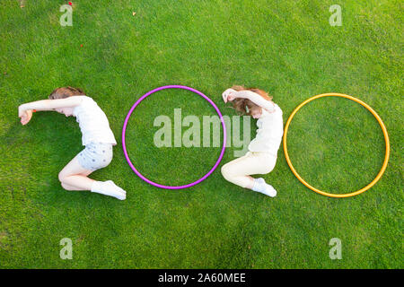 Children for the date of year 2020 with shapes and hula hoops to form the number / numbers twenty 20. (113) - Stock Photo