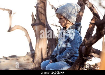 Young boy sitting on a tree at the edge of volcano Ijen, Java, Indonesia - Stock Photo