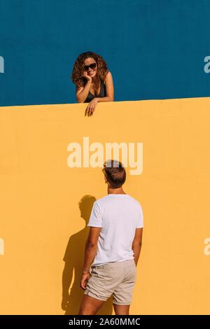 Young man looking at woman behind a yellow wall
