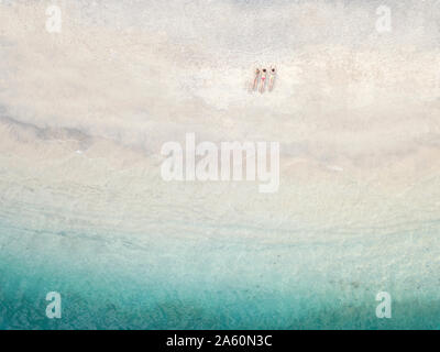 Aerial view of young women lying at the beach, Gili Air island, Bali, Indonesia - Stock Photo