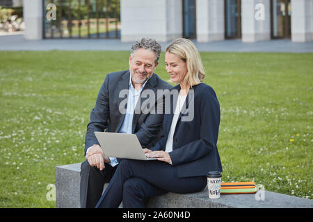 Businesswoman and businessman sitting on a wall in the city using laptop - Stock Photo
