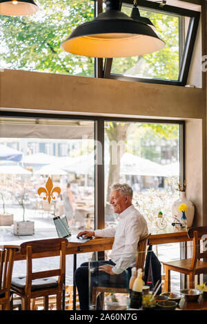 Happy senior businessman using laptop in a cafe - Stock Photo