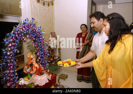 Mumbai, Maharashtra, India, Southeast Asia : Ganpati festival; Idol of Lord Ganesh Pooja (Puja) Performing by Devotees; family before immersion. - Stock Photo